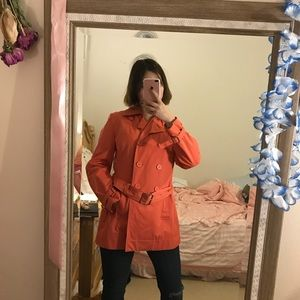 A medium length orangy color trench coat